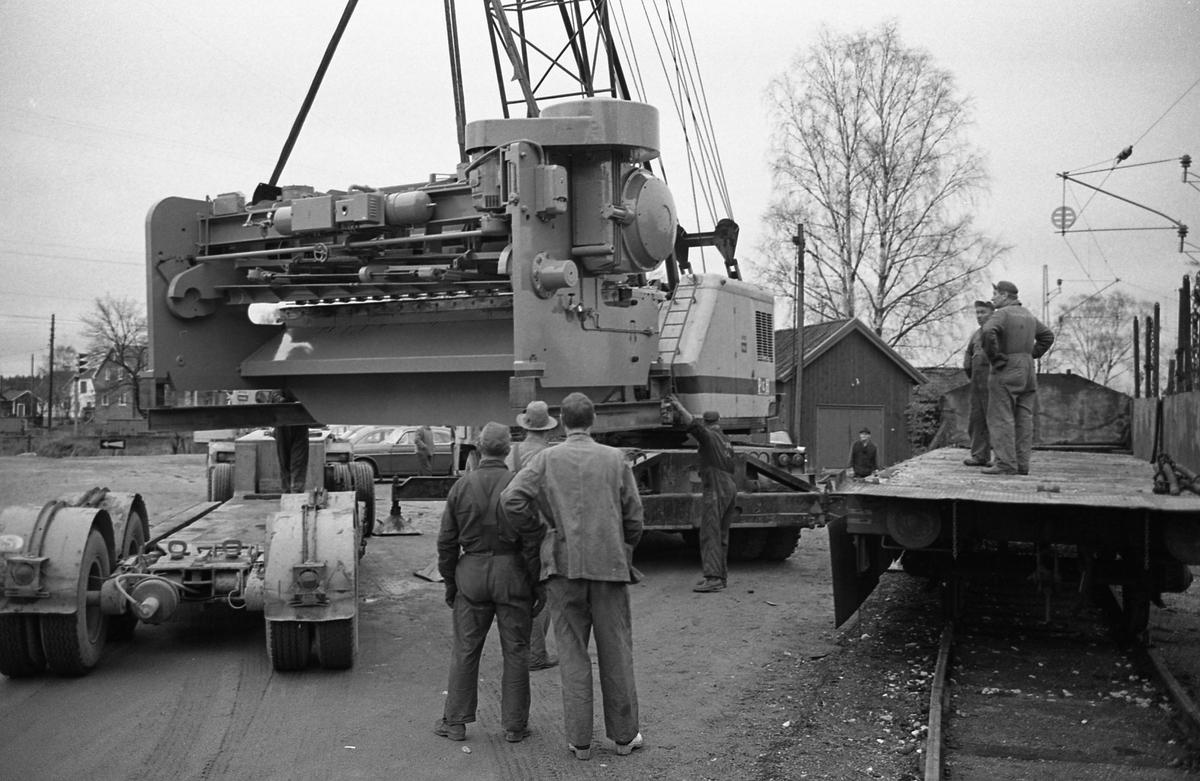 """En lyftkran lastar en gradsax, tillverkad på """"Meken"""", Arboga Mekaniska Verkstad. Transporten ska ske med järnväg.  Män i arbetskläder, lyftkran, järnvägsvagn"""
