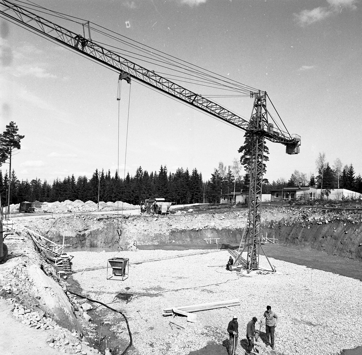Arbeten vid vattenverket. En lyftkran, män med spadar och en cementblandare.