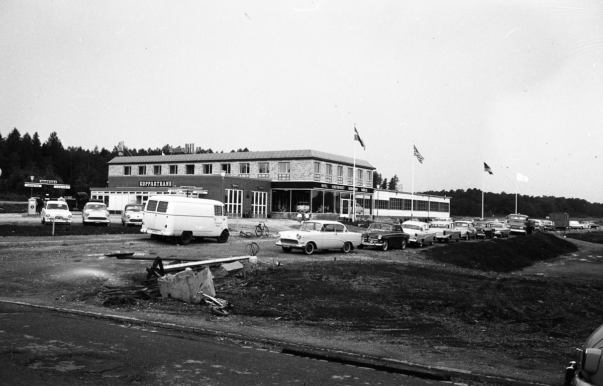 Den nybyggda bilhallen hos Arboga Bil AB. Framför den, ligger bensinstationen Koppartrans. En lång rad bilar är parkerade på Munkgatan. Bilden är tagen från Kapellgatan.