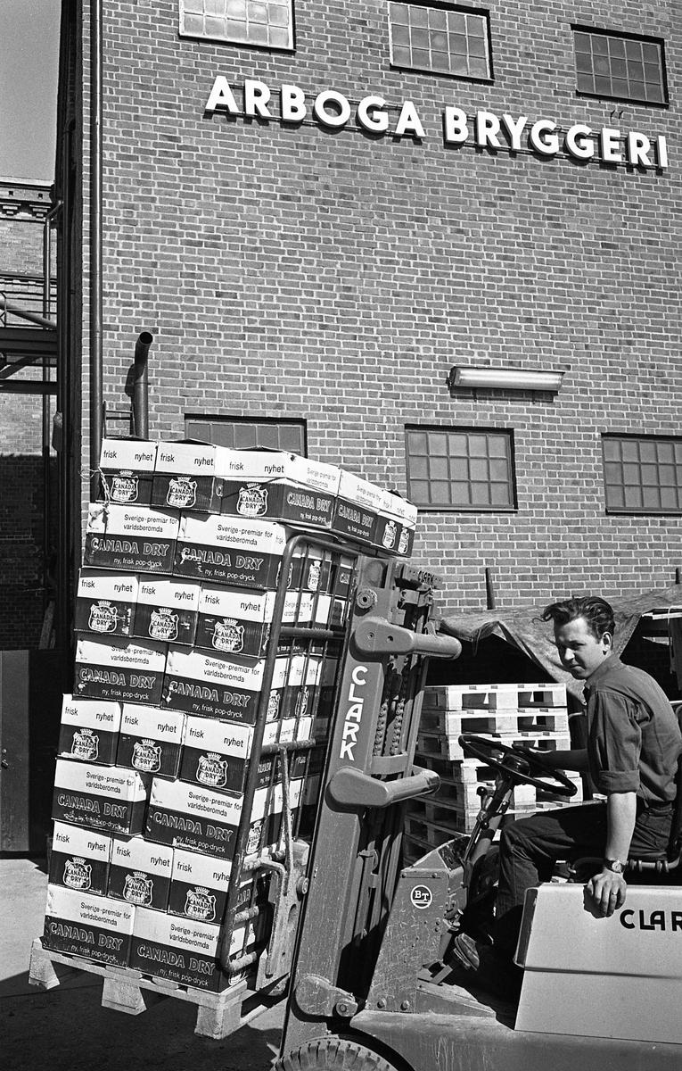 Arboga Bryggeri. En man kör en truck med en lastpall med Canada Dry. Mannen heter Sune Persson.  Anläggningen var färdigbyggd 1899 och verksamheten startade 1 november samma år. 24 oktober 1980 tappades det sista ölet, på bryggeriet. Märket var Dart. Läs om Arboga Bryggeri i hembygdsföreningen Arboga Minnes årsbok 1981