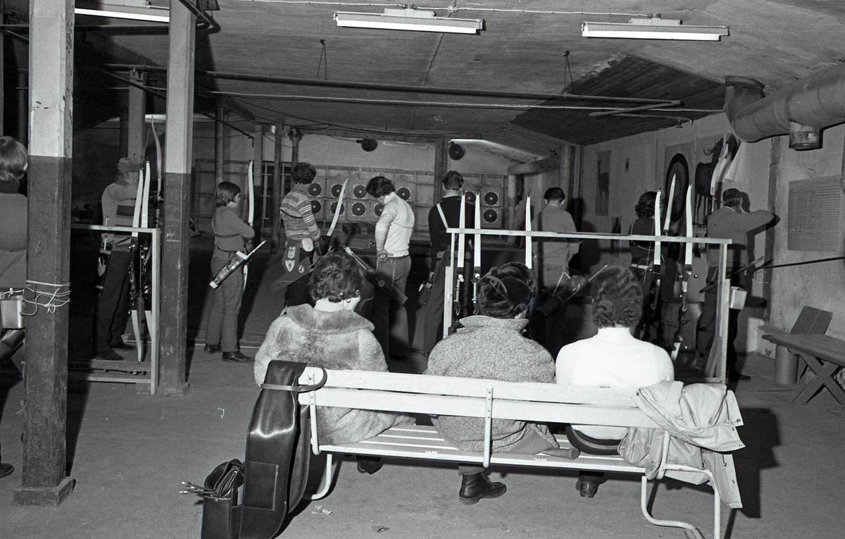 Inomhusövning hos Arboga Bågskytteklubb. Lokalen ser ut att ligga i en källare. Flera personer står på rad och skjuter med pil och båge mot måltavlor på väggen. Alla har sitt koger på höften. Bakom skyttarna står två ställ för pilbågar. På en bänk, med ryggen mot fotografen, sitter tre personer och ser på, två av dem har ytterkläderna på sig.
