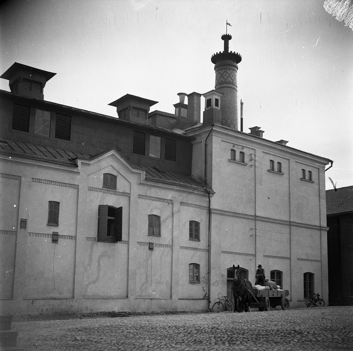 Arboga Kvarn och Maltfabrik, exteriör. Framför byggnaden syns ett ekipage med häst och vagn. Vagnen är lastad med fyllda säckar. Intill väggen står en cykel och en motorcykel. Ett magasin skymtar till höger i bild.  Det som kom att bli Arboga Kvarn och Maltfabrik anlades 1821 av Jonas Örström. Kvarnrörelsen startade 1915. Vetemjöl av märket Guldsnö producerades här.  Kvarnrörelsen upphörde 1967 medan maltproduktionen fortsatte till 1972.  Läs om Arboga Kvarn och Maltfabrik: Hembygdsföreningen Arboga Minnes årsböcker från 1979 och 1999 Reinhold Carlssons bok Arboga objektivt sett