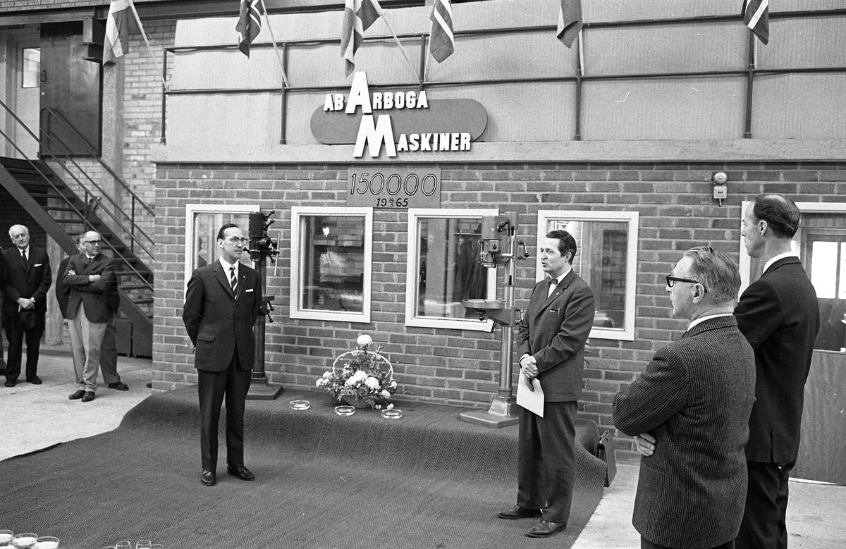 """Arboga Maskiner firar maskin nummer 150 000. Kostymklädda herrar intill ett podium med två pelarborrmaskiner och en blomsteruppsättning. Mannen längst till vänster är Harald """"Hajan"""" Larsson."""