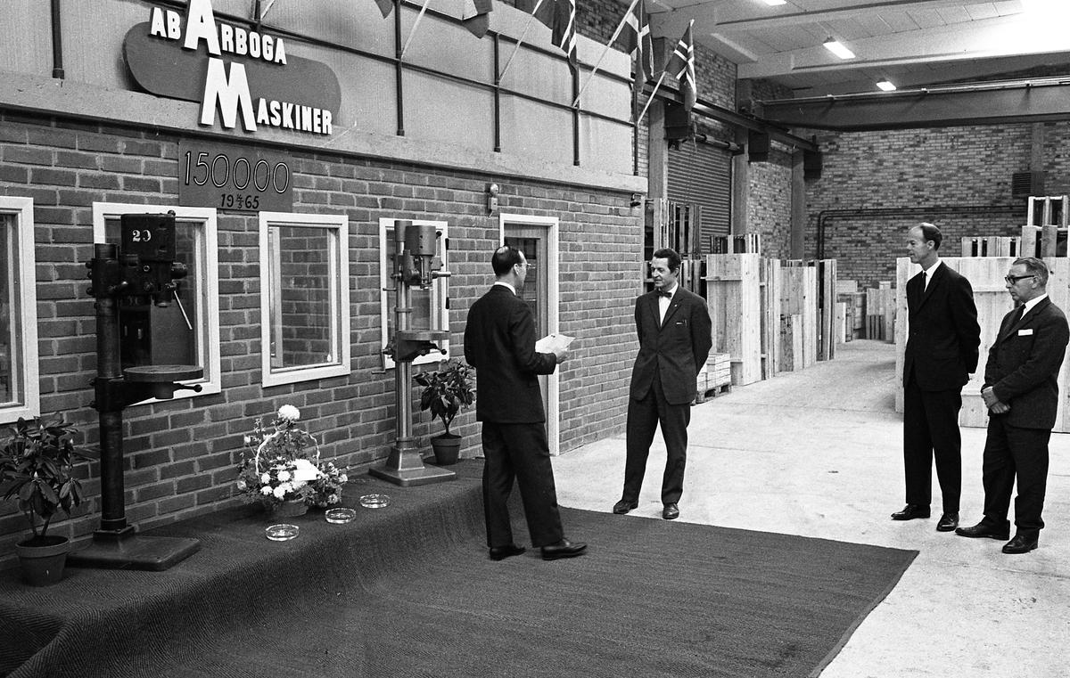 Arboga Maskiner firar maskin nummer 150 000. Fyra kostymklädda herrar vid ett podium med två pelarborrmaskiner och en blomsteruppsättning. En av männen håller ett anförande riktat till en av de andra.  AB Arboga Maskiner startade 1934 och tillverkar borr- och slipmaskiner.