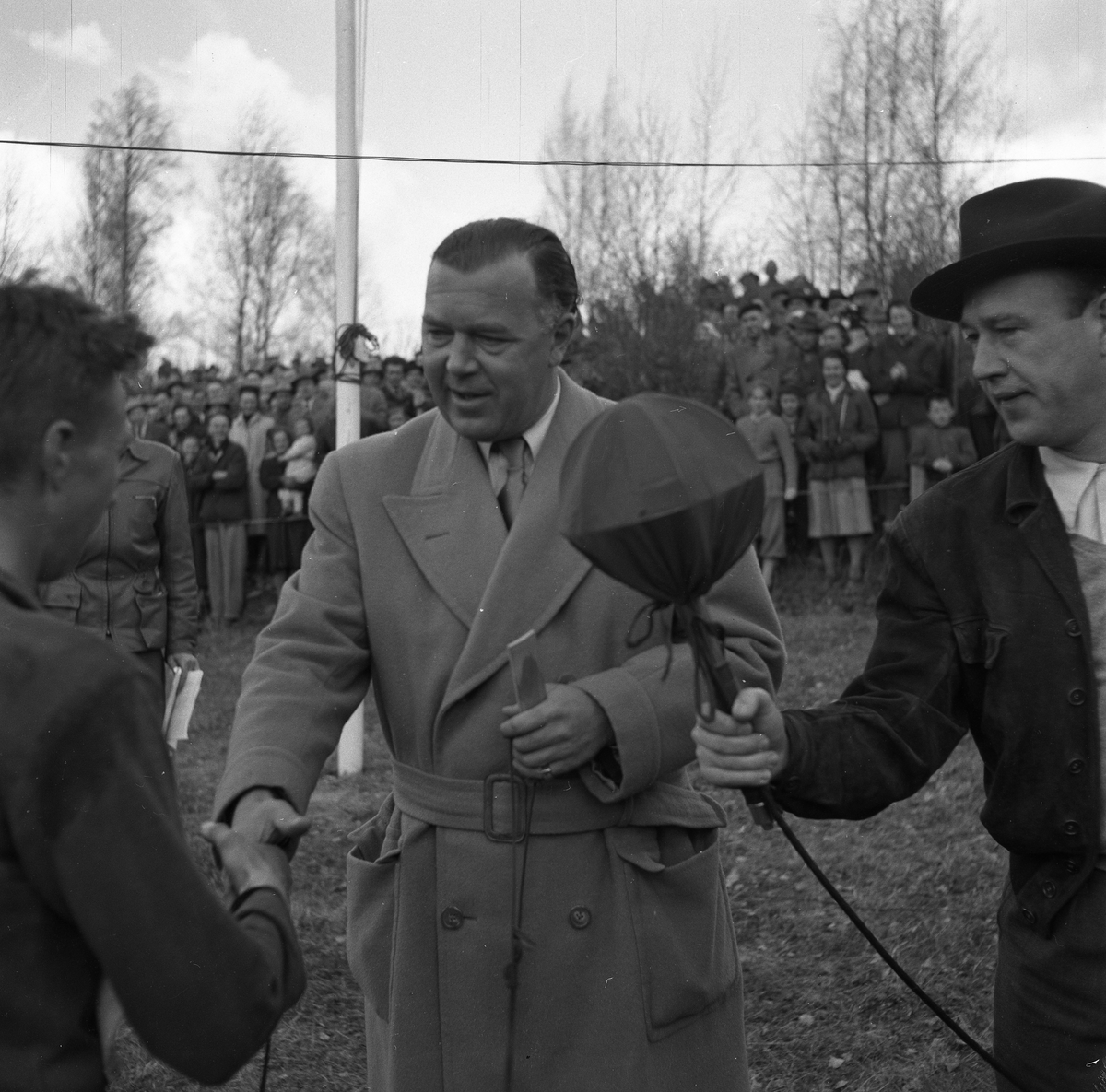 """Arboga Orienteringsklubb har vunnit tiomilaorienteringen. Lennart Öberg, som sprang sista sträckan, gratuleras av Prins Bertil. Lennart Hyland intervjuar för radio. Publiken får hålla sig bakom avspärrningen.  Start: Malmköping. Mål: Bränninge, Södertälje.  Bilder, från detta tillfälle, finns i Reinhold Carlssons bok """"Arboga objektivt sett""""."""