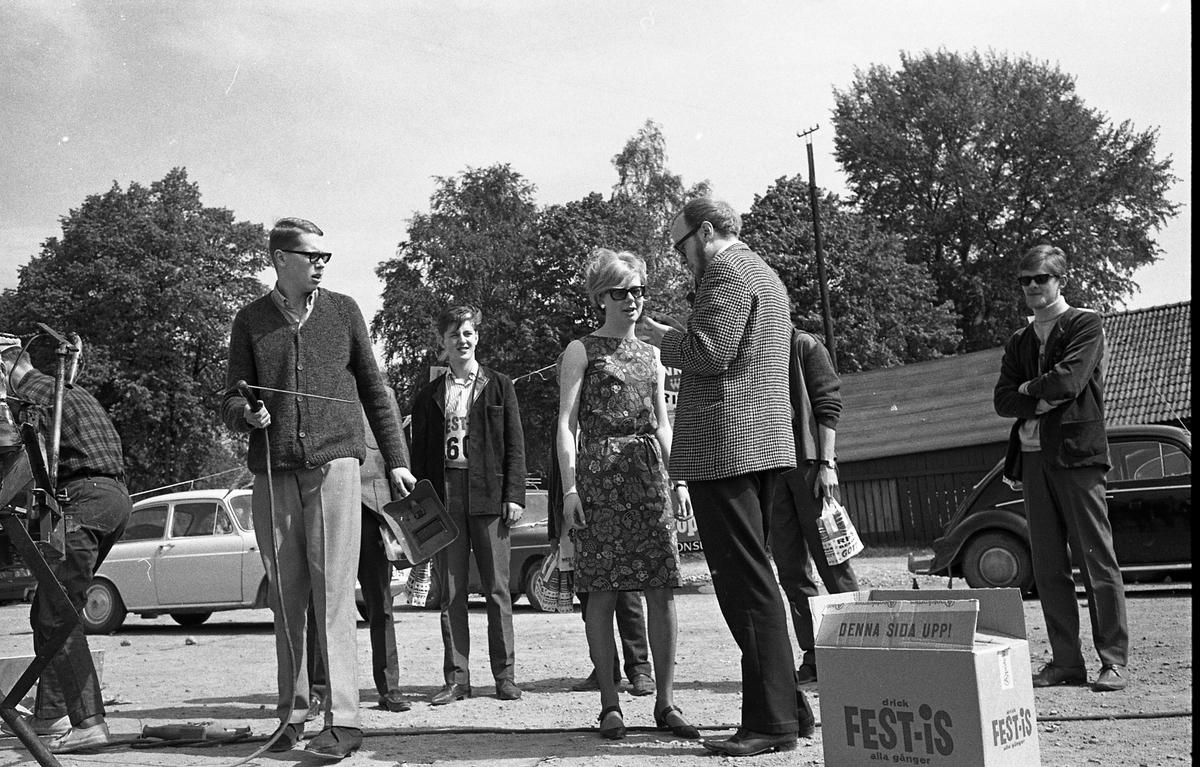 Arboga Tekniska skola, ATS. Äldre elever utsätter nykomlingar för skändning. Längst till höger står Per Bengtsson. En man håller i en svets och en skyddsmask. En låda Fest-is står i förgrunden.