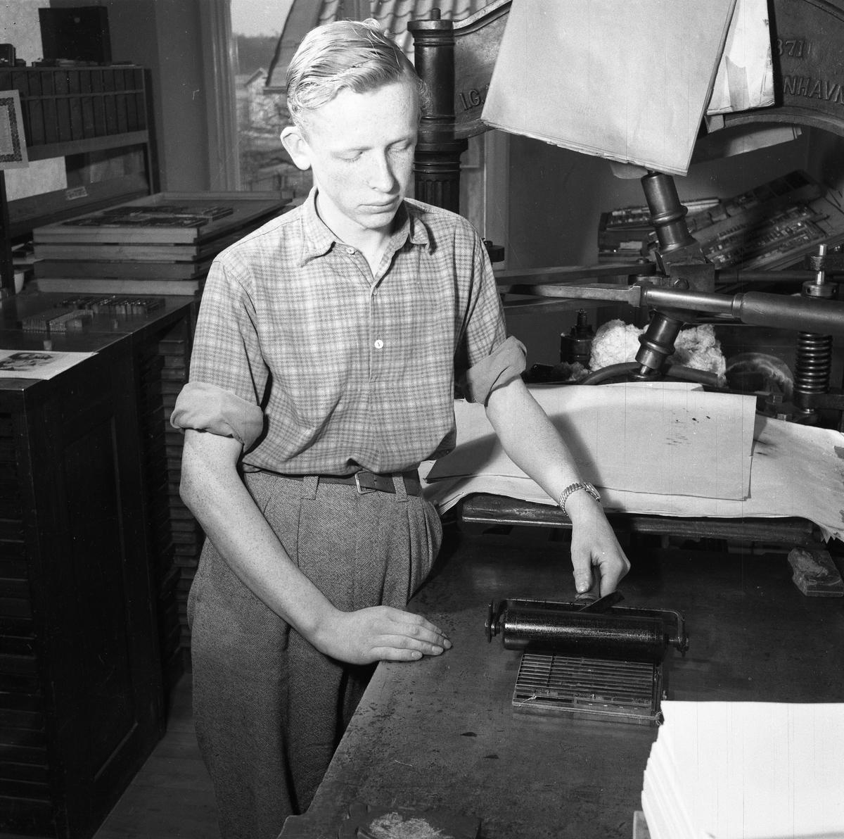 Arboga Tidning, personal och interiör. En ung man arbetar i tryckeriet.