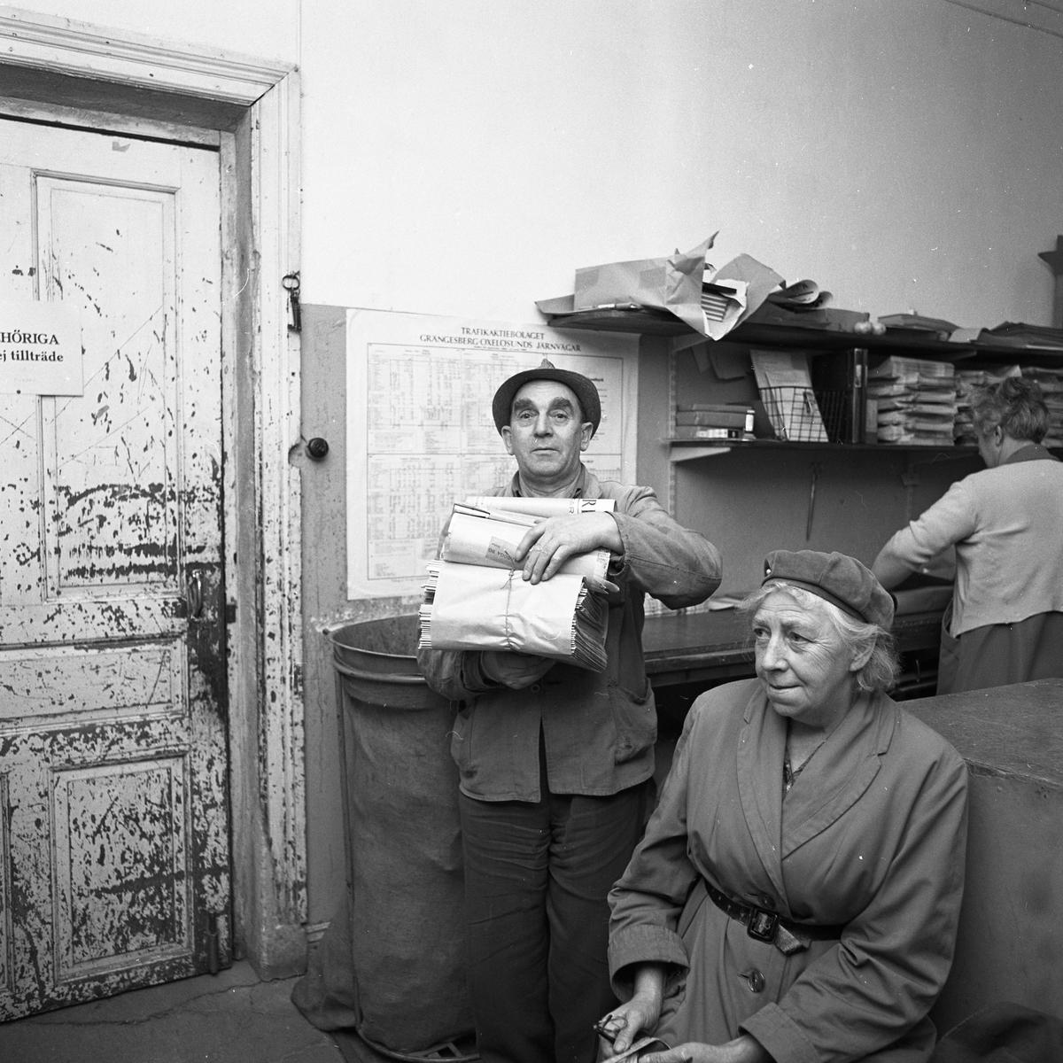 Arboga Tidning distribueras. En man håller en trave tidningar i famnen. I bakgrunden syns en kvinna som packar tidningar. I förgrunden sitter en kvinna, klädd i ytterkäder. Möjligen väntar hon på tåget. På väggen finns TGOJ´s tågtidtabell. Dörren, till vänster, är mycket sliten.