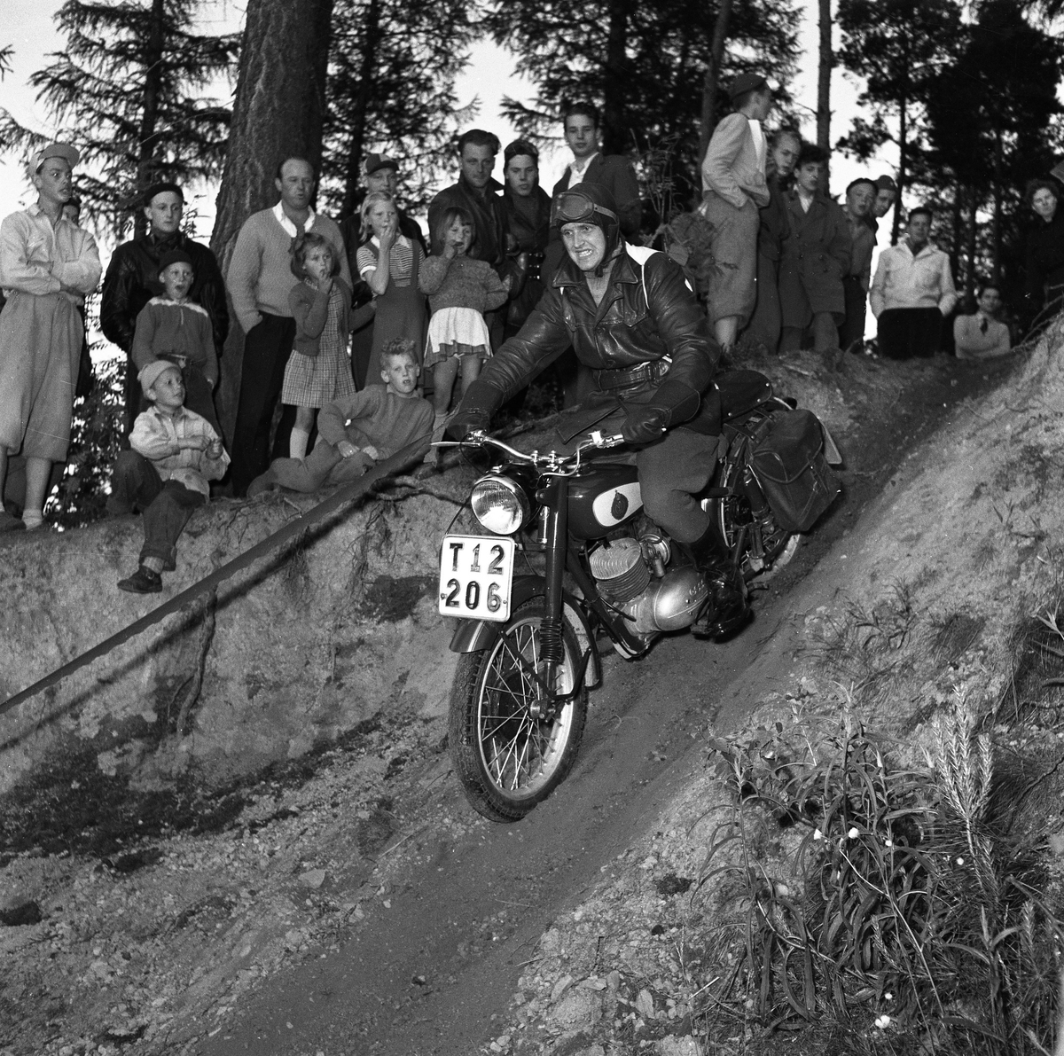 Arbogas Stjärnknutte Tävling i terrängkörning med motorcykel. Man iklädd skinnluva och med vindglasögonen i pannan styr sin motorcykel i nerförsbacken. Motorcykeln har packväskor. Publiken står alldeles intill.