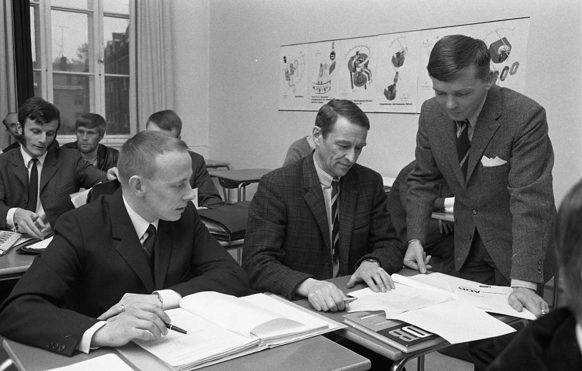 Avslutning på datakurs. Mannen som står upp heter Bertil Sund. Kostymklädda män som sitter i skolbänkar. De har böcker och pärmar framför sig.
