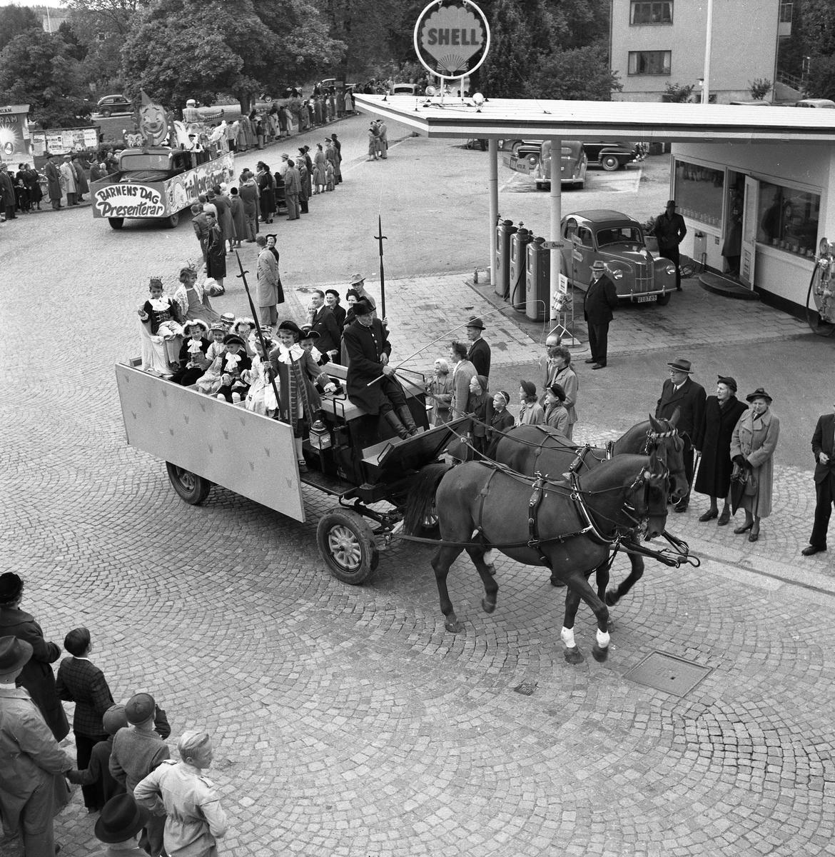 Barnens Dag firas. Två hästar drar en vagn med Barnens Dags Prins och Prinsessa; Erik-Gunnar Larsson och Margareta Lönnberg. Fler utklädda barn sitter på vagnen. En lastbil kommer efter, i paraden. Till höger ses Shells bensinstation vid Jäderstullen. Publiken kantar Jädersvägen.