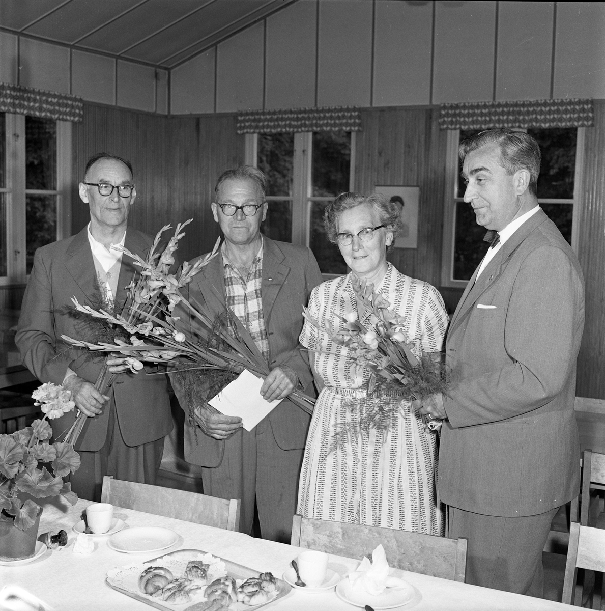 Pensionsavtackning på CVA. Två män och en kvinna uppvaktas med blommor av chefen. Bordet är dukat för kaffe och bullar. I en kruka står en pelargon. Längst till vänster: Nils Andersson. Längst till höger: Anders Högfeldt.