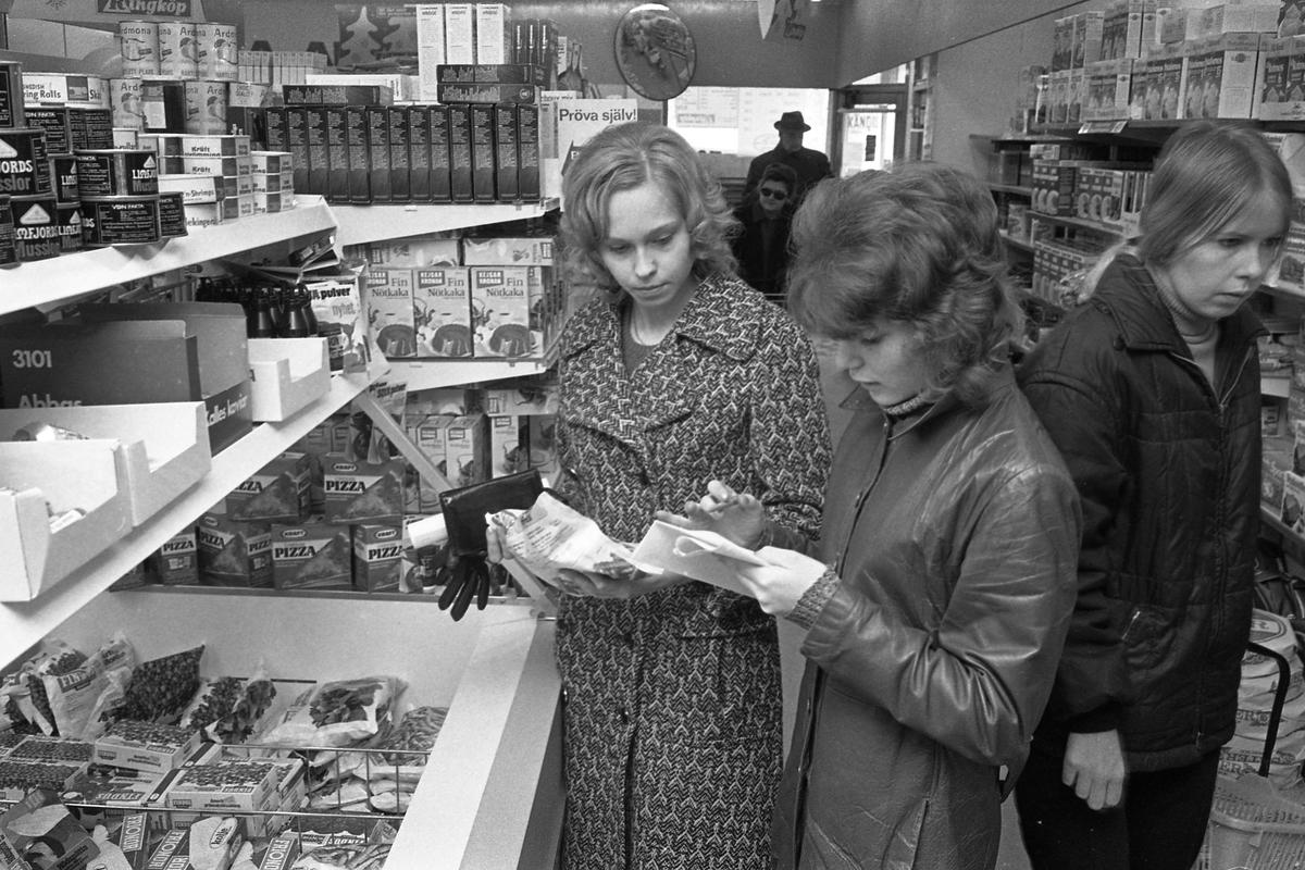 Två elever studerar priser i frysdisken på mataffären Ringköp. Den vänstra flickan är Eva Sörensen. Andra kunder skymtar i affären.