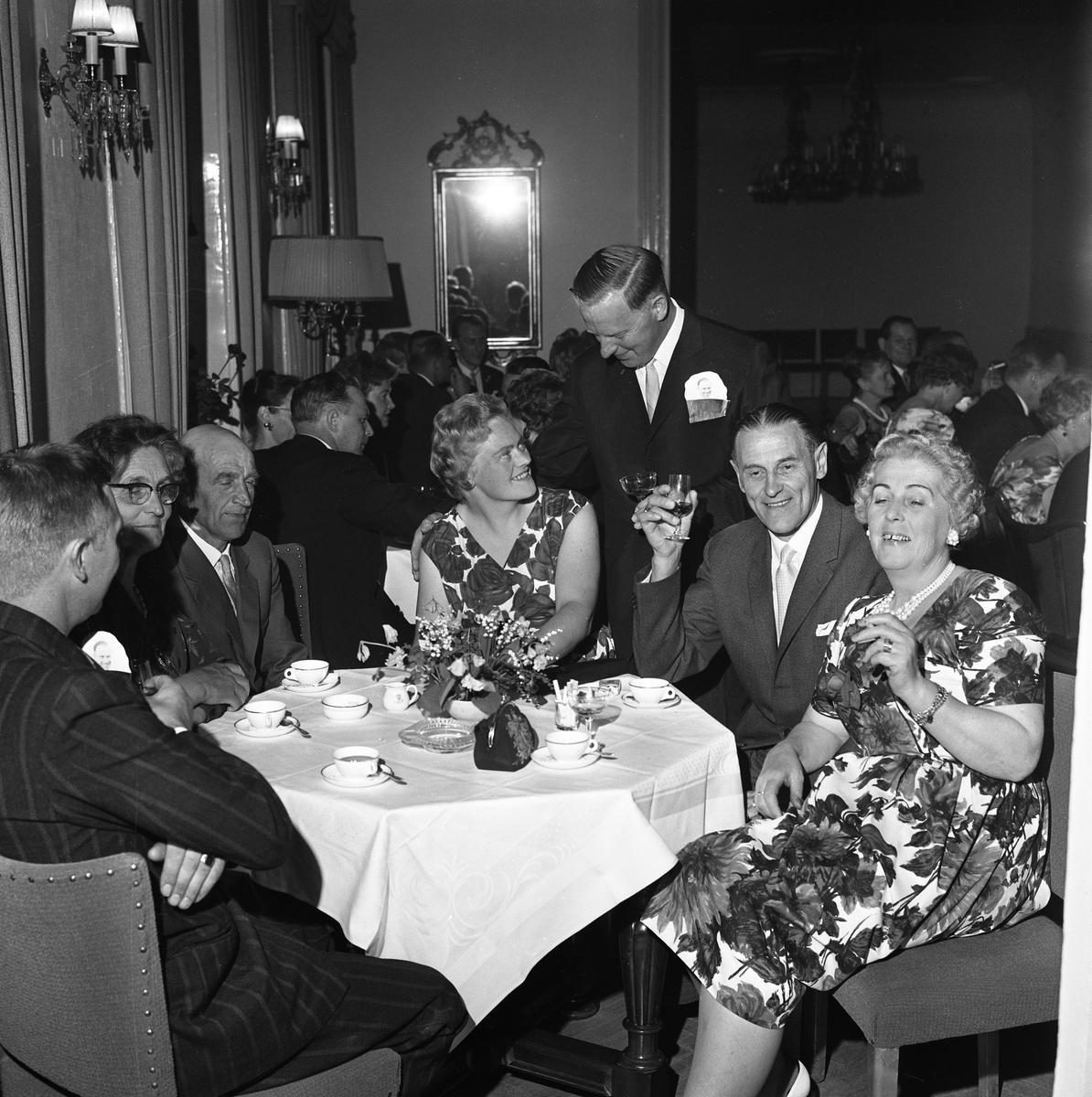 """Erik Holms (""""Glass-Holms"""") 50-årskalas. Erik samtalar med sina gäster. Kvinnan längst till höger är Solveig Berggren. Festklädda människor, kaffekoppar på borden."""