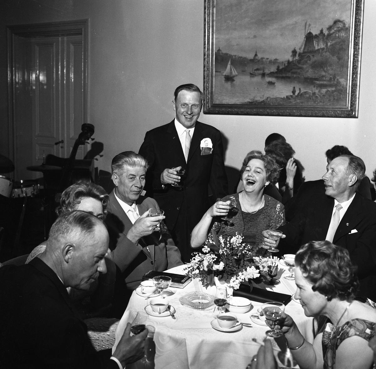 Erik Holm (kallad Glass-Holm) har 50-årskalas, han möter fotografens blick. Här sitter några glada vänner vid ett bord. De har glas i händerna. Kaffekopparna står på bordet. Kvinnan, i bildens nedre högra hörn, är Eriks hustru, Berta Holm. Bakom gästerna ses musikinstrument.