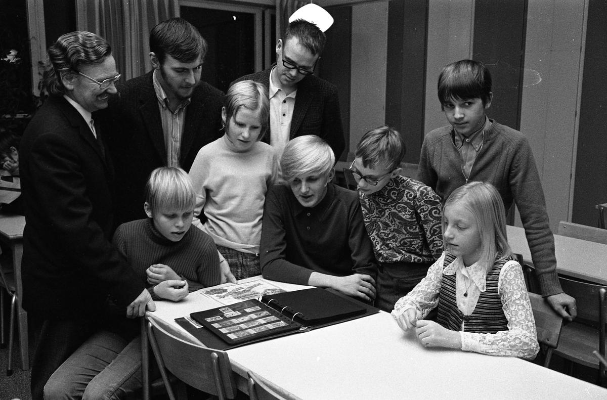 Frimärksklubben. Män, ungdomar och barn tittar i ett frimärksalbum. Mannen längst till vänster heter Erik Östlund.