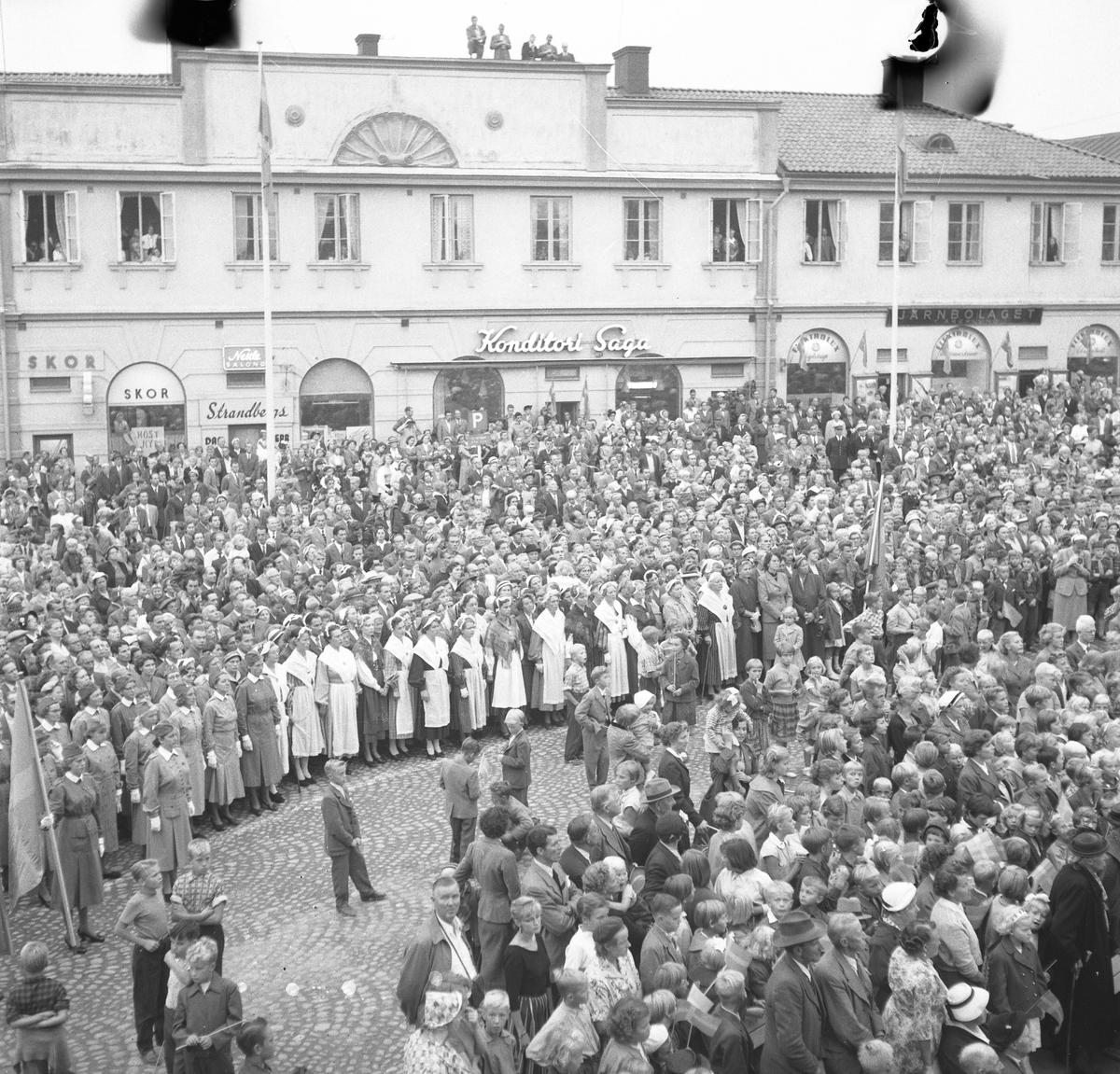 Människor har samlats, på Stora torget, för att se och höra kung Gustaf Vl Adolf. Han gästar Arboga under sin Eriksgata. I publiken ses Arboga Lottakår, kvinnor i folkdräkt, Arboga Scoutkår, gamla och unga. Några har klättrat upp på taket på Lungborgska fastigheten. I bakgrunden ses skoaffären, Strandbergs (Atchy Strandbergs frisersalong), Konditori Saga och Järnbolaget. För värdskapet svarade stadsfullmäktiges ordförande Jonas Carlsson och kommunalborgmästare Danliel Ekelund. Den organisationskommitté som ansvarade för arrangemangen, hade hos drätselkammaren begärt en summa av 3000 kronor för att täcka kostnaderna vid kungabesöket. Beloppet beviljades.  Tiden för kungens besök var beräknad till 130 minuter.