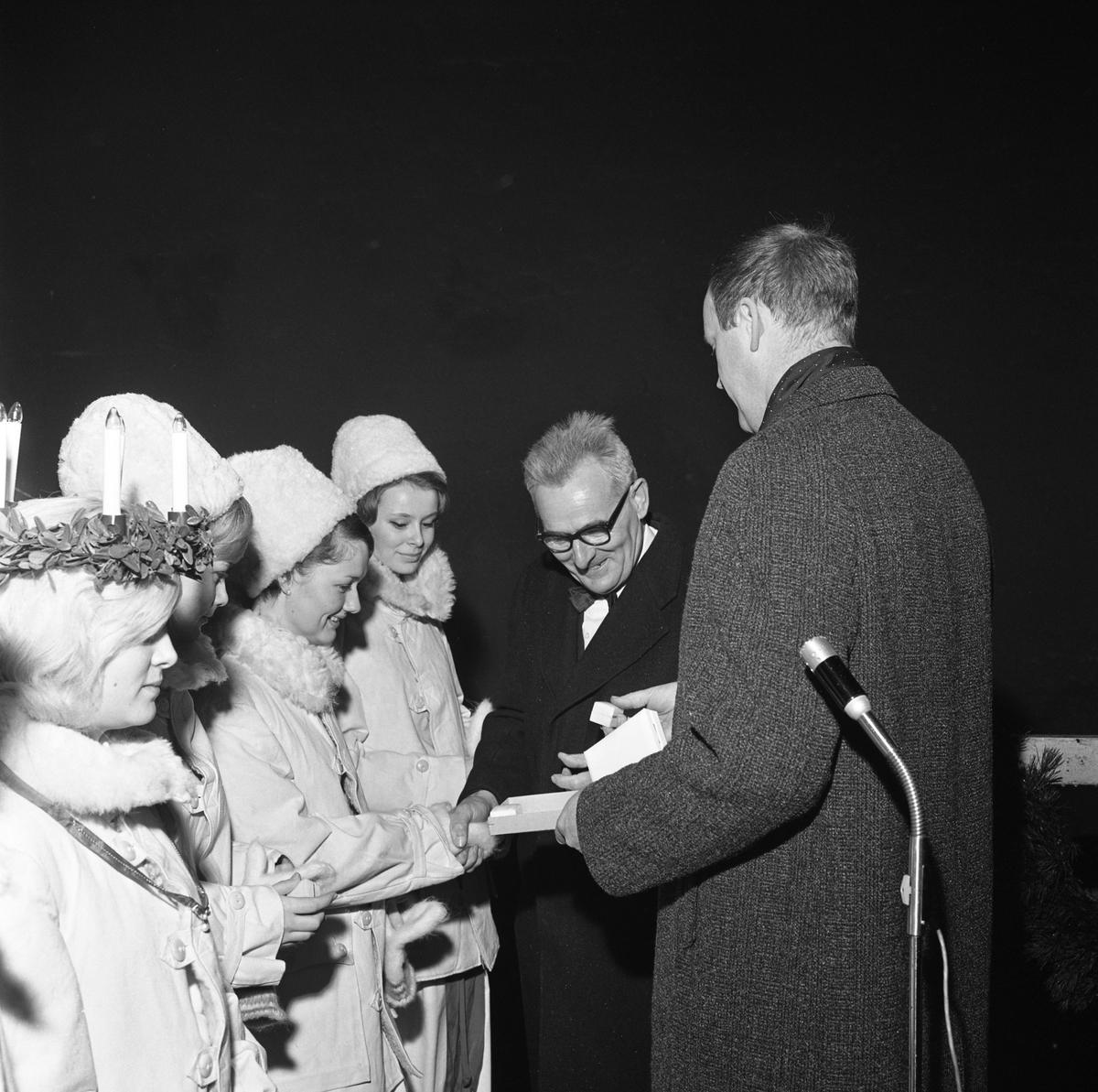 Luciakröning av stadsfullmäktiges ordförande, Jonas Carlsson. Lucia och tre tärnor, iklädda vinterjackor. Tärnorna har pälsmössor.