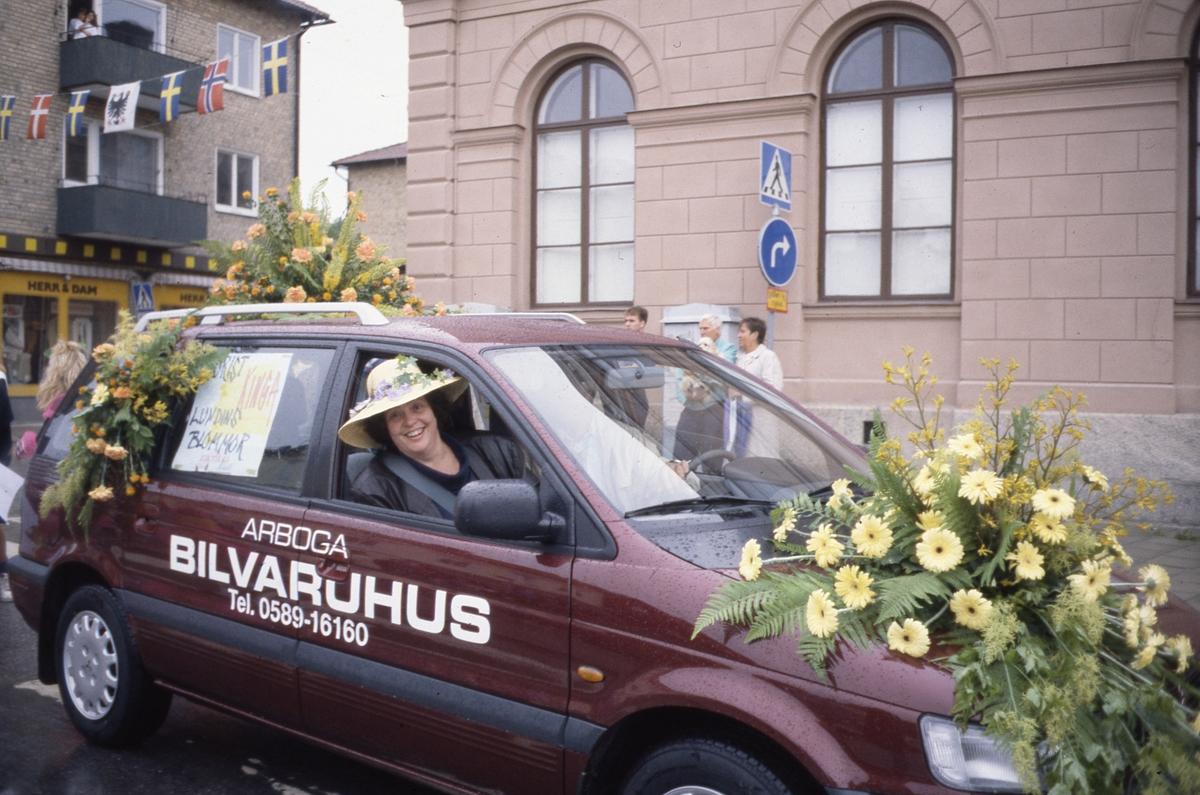 Arbogakarnevalen. Paraden har nått Hökenbergsgränd. Här kommer en bil dekorerad med blommor från Lundins blommor. På passagerarsätet sitter Ulla Lundin. Byggnaden i bakgrunden är Nikolai kulturhus.