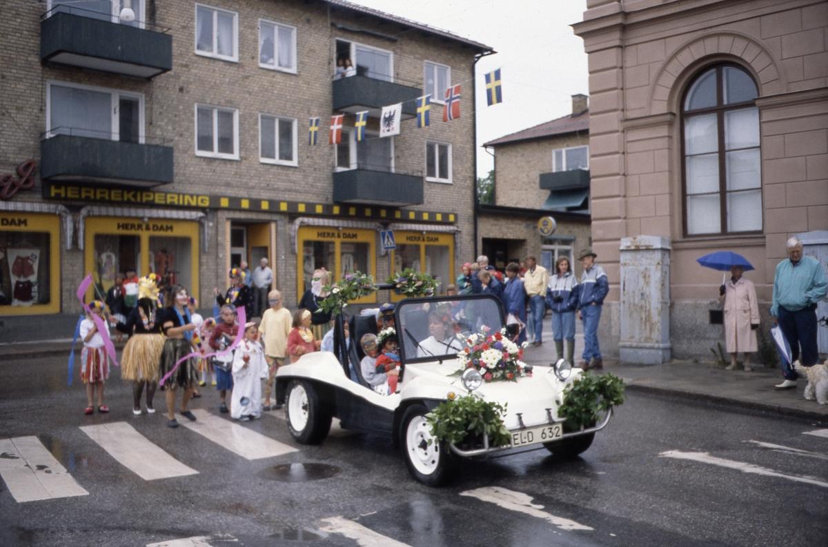 Arbogakarnevalen pågår. Paraden svänger av Nygatan och in på Hökenbergs gränd. Här ses en blomsterdekorerad bil med utklädda barn i och bakom. Till vänster ses Sandbergs herrekipering. I hörnet, vid Nikolai skola/Nikolai Kulturhus står publiken. I lika dana regnjackor; Lotta Winkler Yngve och Olof Yngve. Mannen längst till höger, i ljusblå jacka, är Per Erik Bruksner.