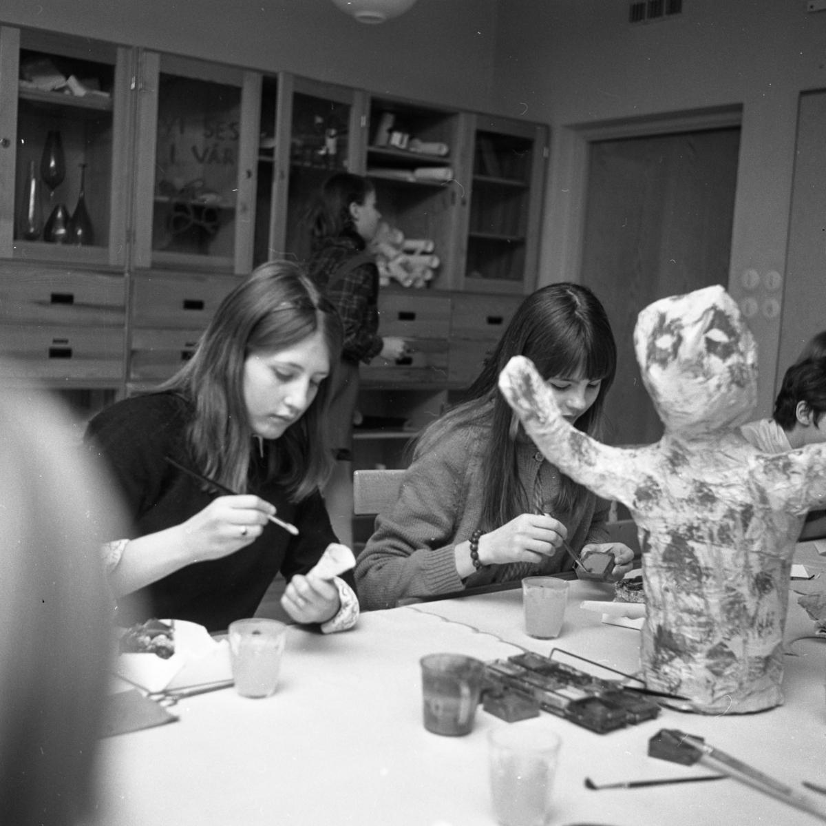 NA NT Teckningskurs på Stureskolan. Vid bordet sitter Annica Karlsson och Eva Nyberg. På arbetsbordet finns vattenfärger och penslar samt en figur av papier mache. Bakom flickorna ses skåp med material.