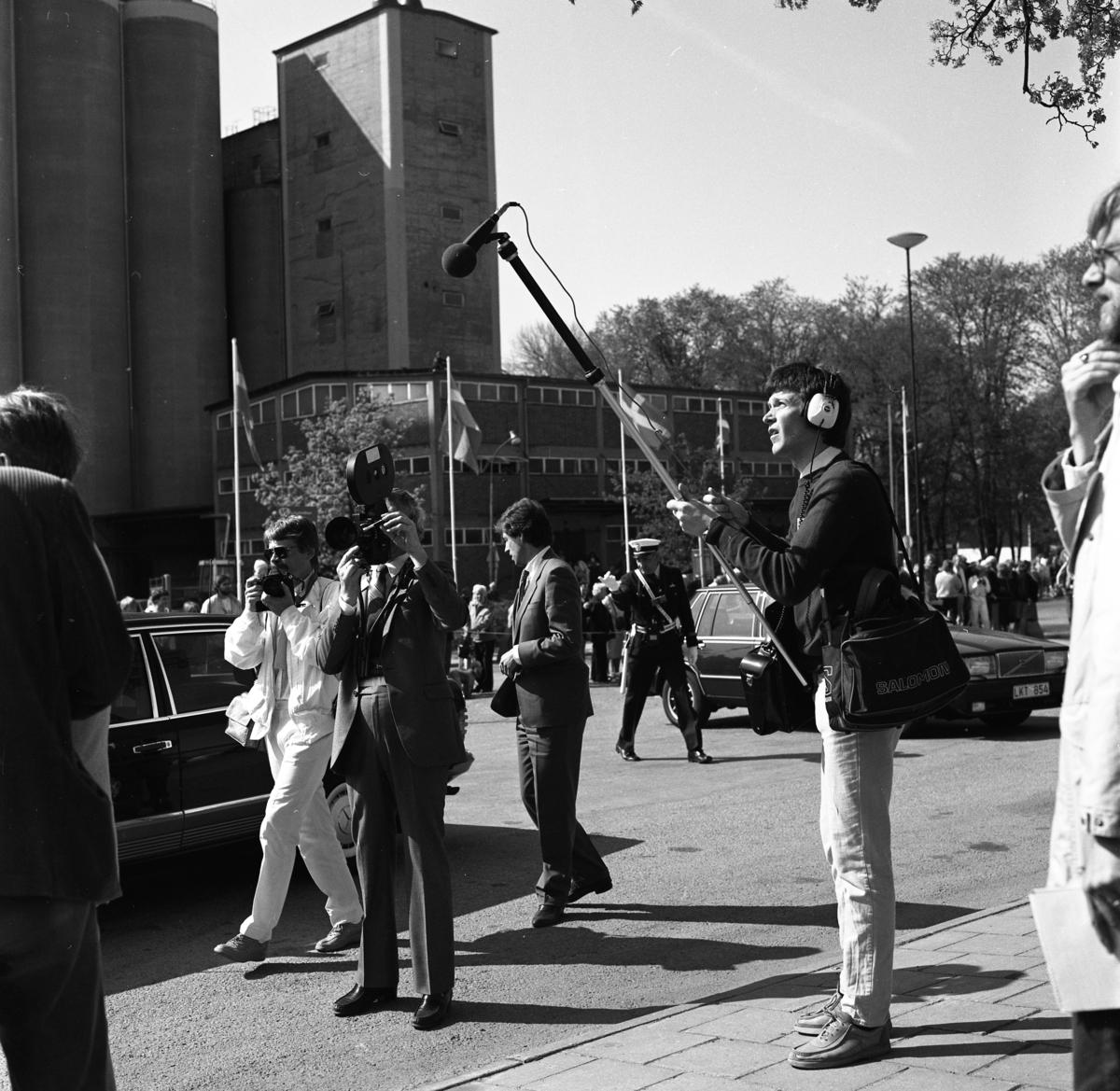 Pressen och polisen vid järnvägsstationen. Allmänheten trängs för att se kungaparet och riksdagsledamoterna som anländer med tåg. Den ljusklädde fotografen är Björn Johansson på Arboga Tidning. I Arboga firas 550-årsminnet av Sveriges första riksdag. Riksdagsjubileet 1985. I bakgrunden ses Lantmännens silo.