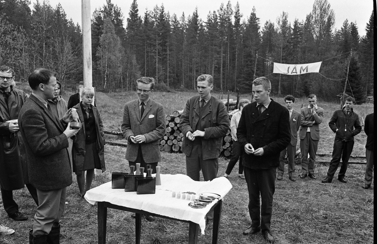 Scouternas budkavle-FM. Prisutdelning utomhus, intill målgången. Tre unga män står framför prisbordet, andra ungdomar tittar på.