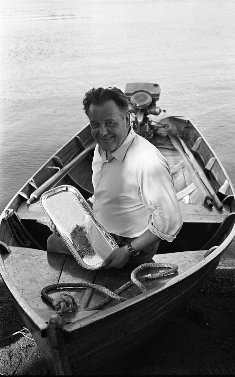 Segrare i motorbåtstävling. Man som sitter i fören på sin båt. Han håller en bricka i handen. Brickan är nog hans förstapris.