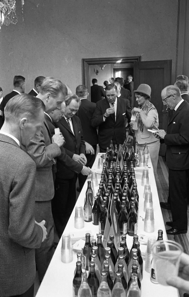 Statsutskottet besöker Arboga. Här får de förfriskningar. Platsen är rådhuset. Poliltikerna köar vid ett långbord dukat med dricksflaskor.