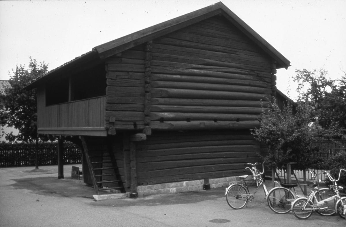 Timmerhuset bakom museet. Hitflyttat. Loftgång.  Bredvid står ett ställ med cyklar. Smedjegatan till vänster.