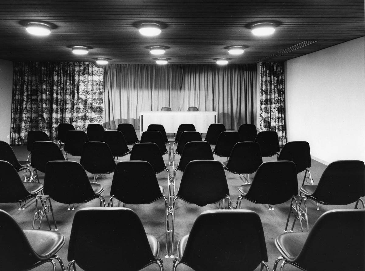 Arboga Stadsbibliotek, interiör. Hörsalen en trappa ner. Uppställda plaststolar i förgrunden. Längst bak, i bilden, ses podiet med draperier / ridåer.