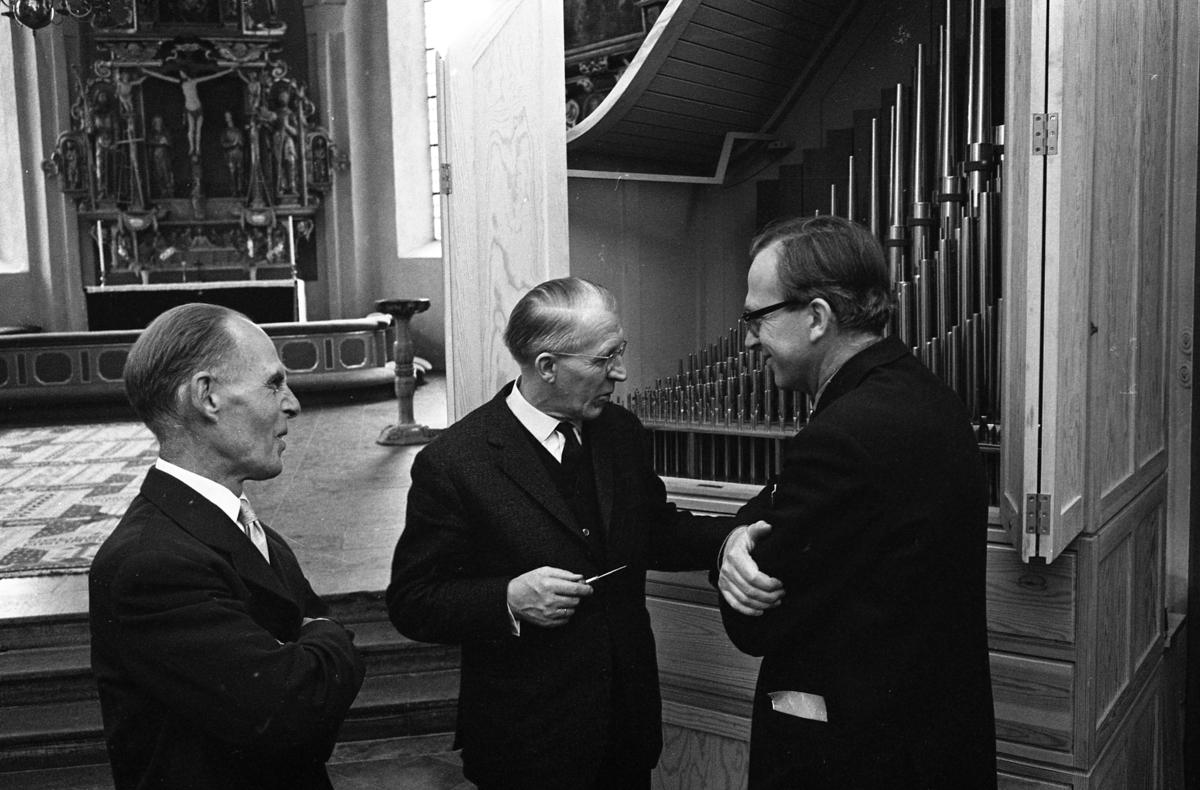 Heliga Trefaldighetskyrkan inspekteras. Interiör. Här studeras orgelpiporna. Till vänster Ture Berggren (eventuellt Gustav Berggren) och till höger Bertil Stoltz. I bakgrunden ses altaret, altartavlan och dopfunten.