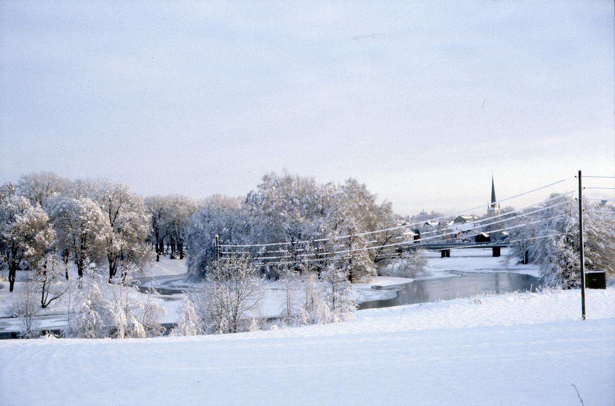 Vintervy över staden, sedd från Törnberget. Is på Arbogaån. Strömsnäsbron och Heliga Trefaldighetskyrkan. Snötäckt landskap.