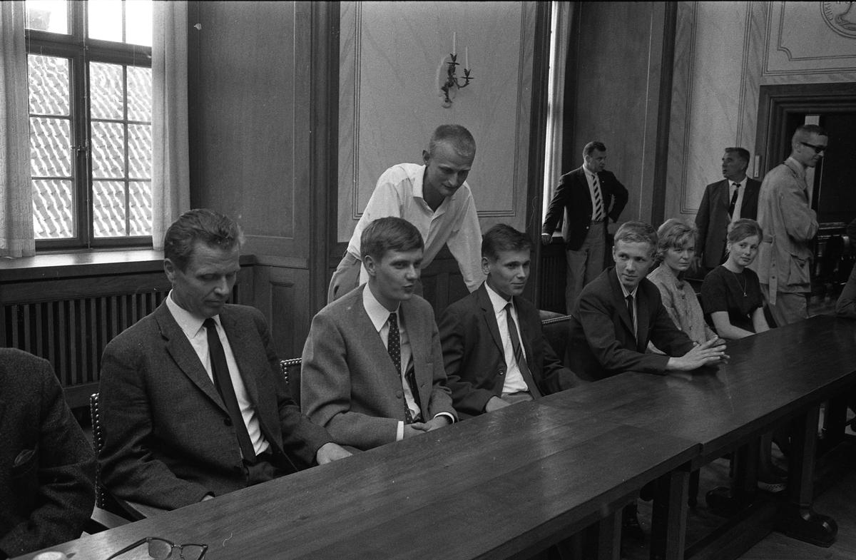 """Vänortsbesök från Hollola. Hans Jansson (""""Kniven"""") i vit skjorta och vid dörren står Nils Brodin. Bilden är tagen i kommunfullmäktigesalen på Rådhuset."""
