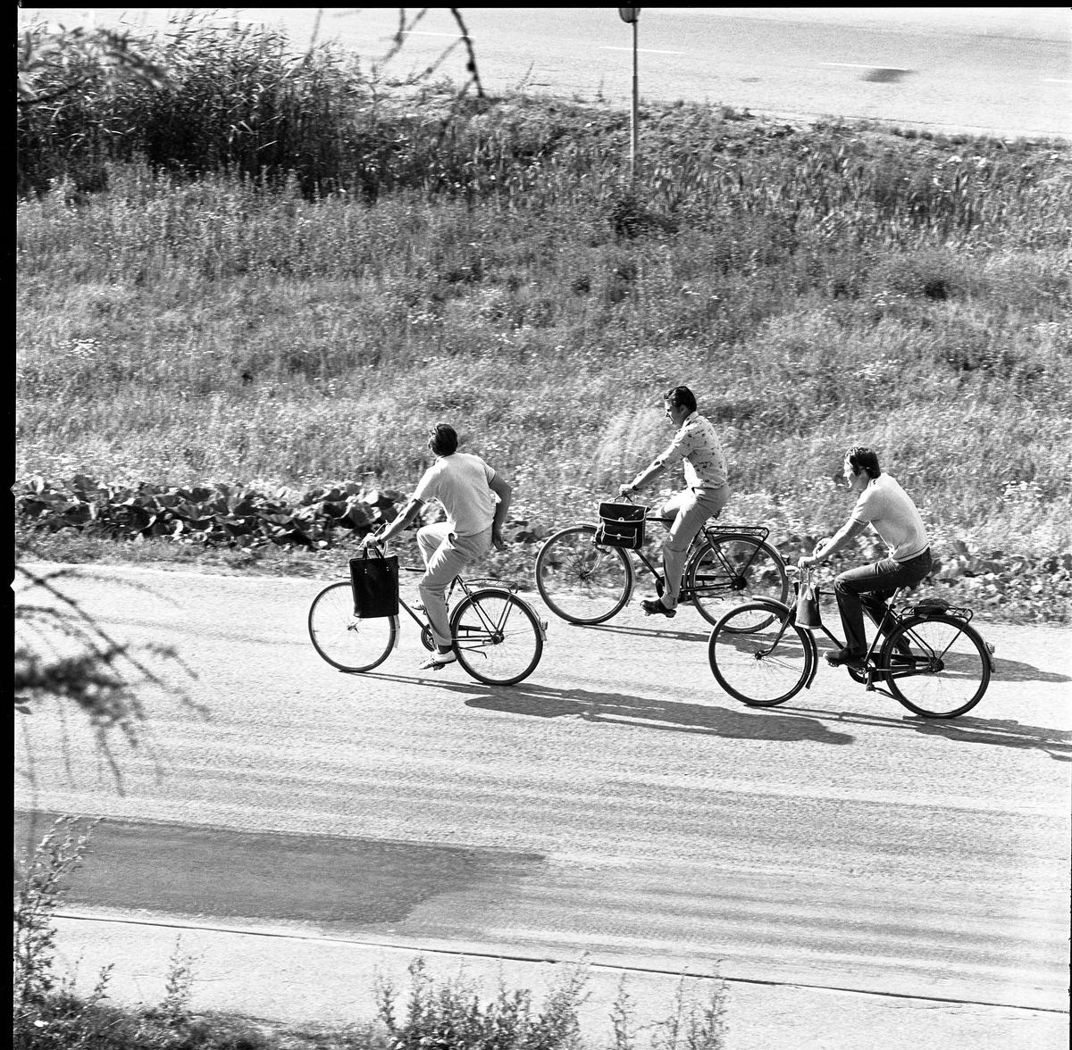 Västermovägen. Tre cyklister på väg uppför Brattbergsbacken.