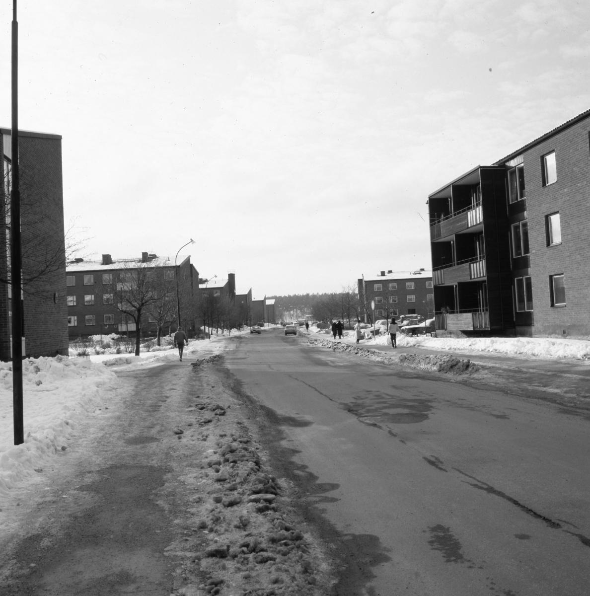 Österled med flerfamiljshus på båda sidor. Människor och bilar i rörelse. Vinter och snö.
