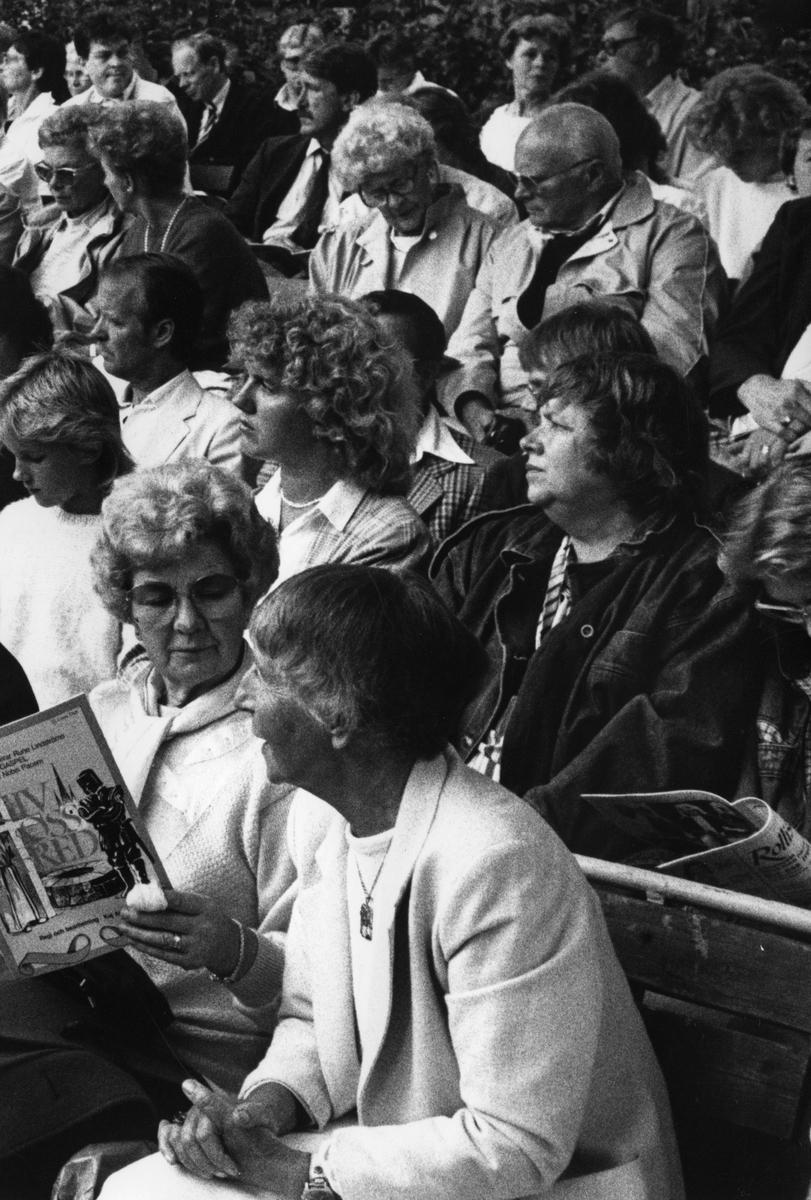 """Publikbild från skådespelet """"Giv oss Fred"""". En kvinna håller i programhäftet. Inger Kanders ses mitt i bild. Publiken sitter utomhus, på museigården.""""Giv oss fred"""", även kallat """"Arbogaspelet"""", är ett teaterstycke skrivet av Rune Lindström 1961. Handlingen, som är inspirerad av Arbogas klosterhistoria, är förlagt till början av 1500-talet. Uruppförandet skedde den 11 augusti 1962 och Rune Lindström spelade Engelbrekt Gertsson. Lions Club i Arboga stod för arrangemanget. Föreställningarna regnade bort och det blev ett stort ekonomiskt bakslag för föreningen. Spelet har framförts igen; 1987, 1988, 2012 och 2015 av medlemmar i """"Bygdespelets Vänner""""."""