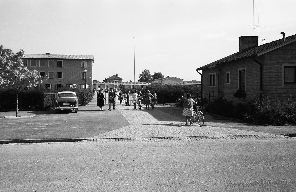 """Infarten till Gäddgårdsskolan. Människor i rörelse. En bil står parkerad. Fotografen har angivit att bilden ingår i """"Dokumentation av fastigheter söder och norr om ån. Bilder och beskrivningar finns på Arboga Museum""""."""