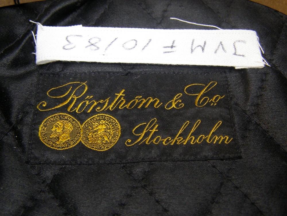 Uniformsmössa av mörkblått kläde med 3x3 mm gul galon, nationalkokard av metall, svart stormtränsrem mellan guldknappar. Mössmärke för SJ i form av ett bevingat hjul med krona.