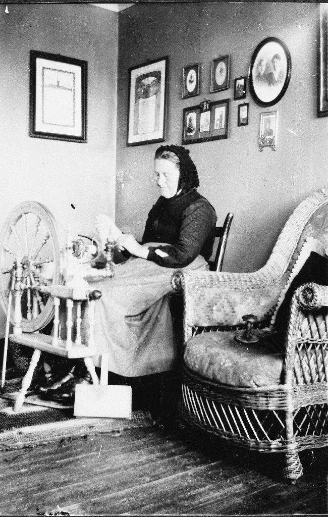 Interiørbilete frå oppsettstova på Tjensvoll. Marta Maria (Maja) Tjensvoll f. Fotland (1849 - 1933) sit ved rokken og spinn. På veggen heng diplomar for landbruksvarer som fatost og smør og for kvitlar (ullteppe).