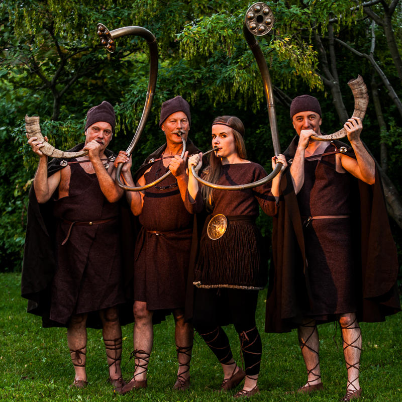 Fire mennesker kledd i bronsealderklær står og blåser i hvert sitt bukkehorn eller bronselur.