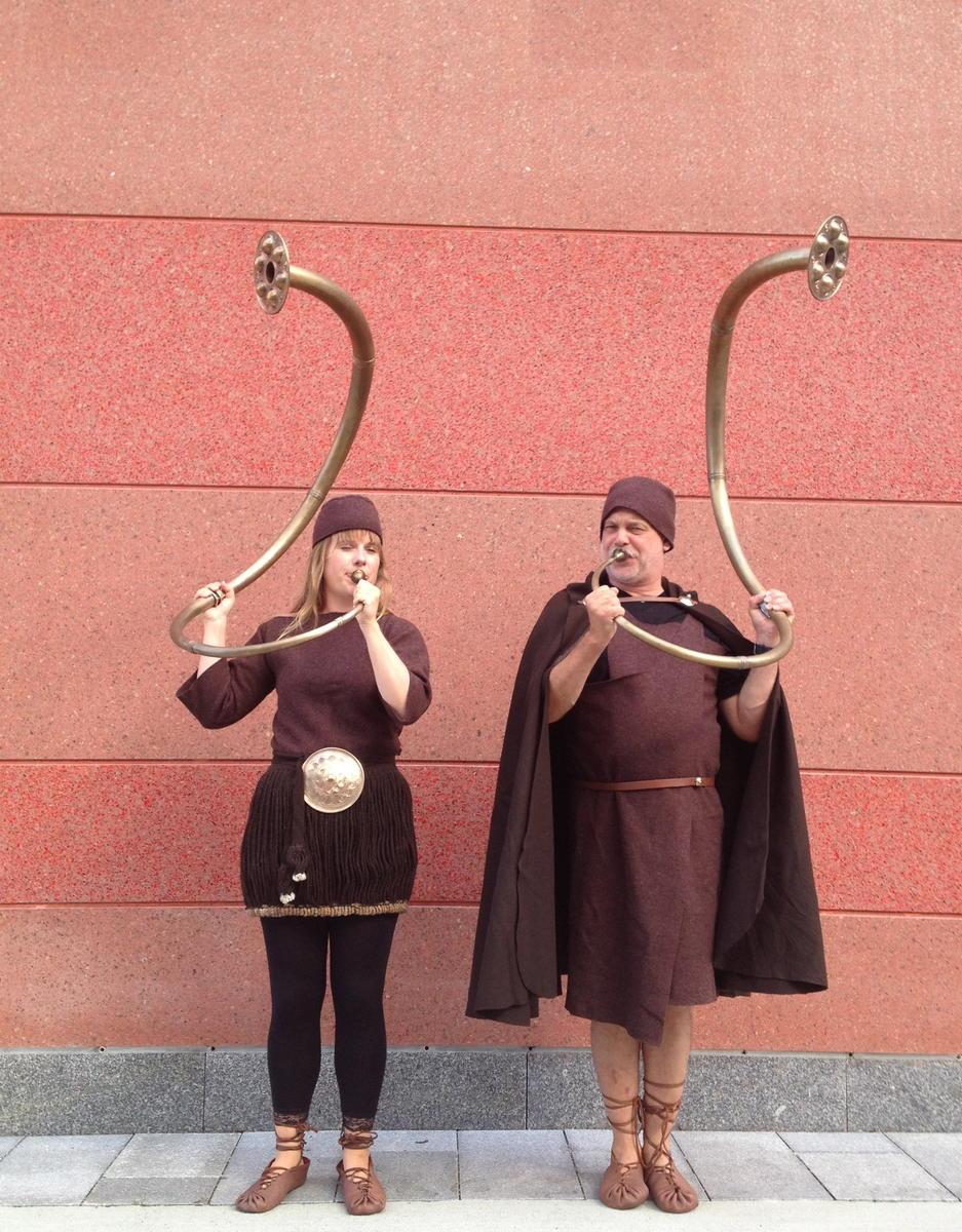 To bronsealderkledde mennesker står foran en rødlig murvegg og blåser i hver sin bronselur.