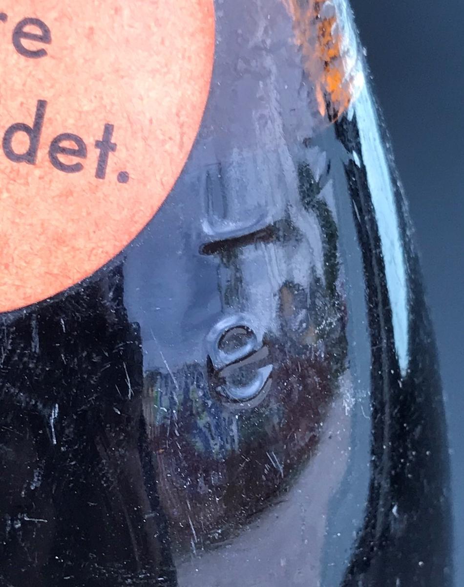 """Knoppölflaska som används till Bosco skomakarebläck.  Flaskan tillverkades huvudsakligen till öl av olika alag, men användes bevisligen även till andra produkter. Flaskan är förseglad med kork och snöre. Etikett: Beige med text """"Bosco skomakarebläck [...] Boston Blacking Company // Hälsingborg Sweden"""""""