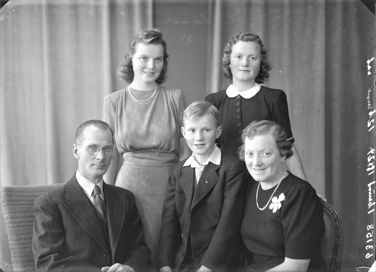 Gruppebilde. Familiegruppe på fem. Bakerst står to unge mørkhårede kvinner. den ene i lys, farget kjole og perlekjede om halsen. Den andre i mørk kjole med hvit krage og store knapper i front. Foran fra venstre en voksen mann med briller i stripet dress og vest. hvit skjorte og farget slips. Ung lyshåret gutt i mørk dress med hvit skjorte. Til høye en voksen kvinne i mørk kjole med hvit blomsterbroderi på venstre side av brystet, perlekjede om halsen. Bestillt av Thorleif Bjølgerud. Breidablikgt. 145