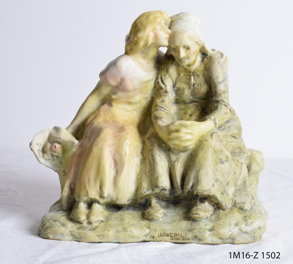 Skulptur som visar två kvinnor, en ung som håller om den äldre. Den unga håller även en bukett blommor i den högra handen.