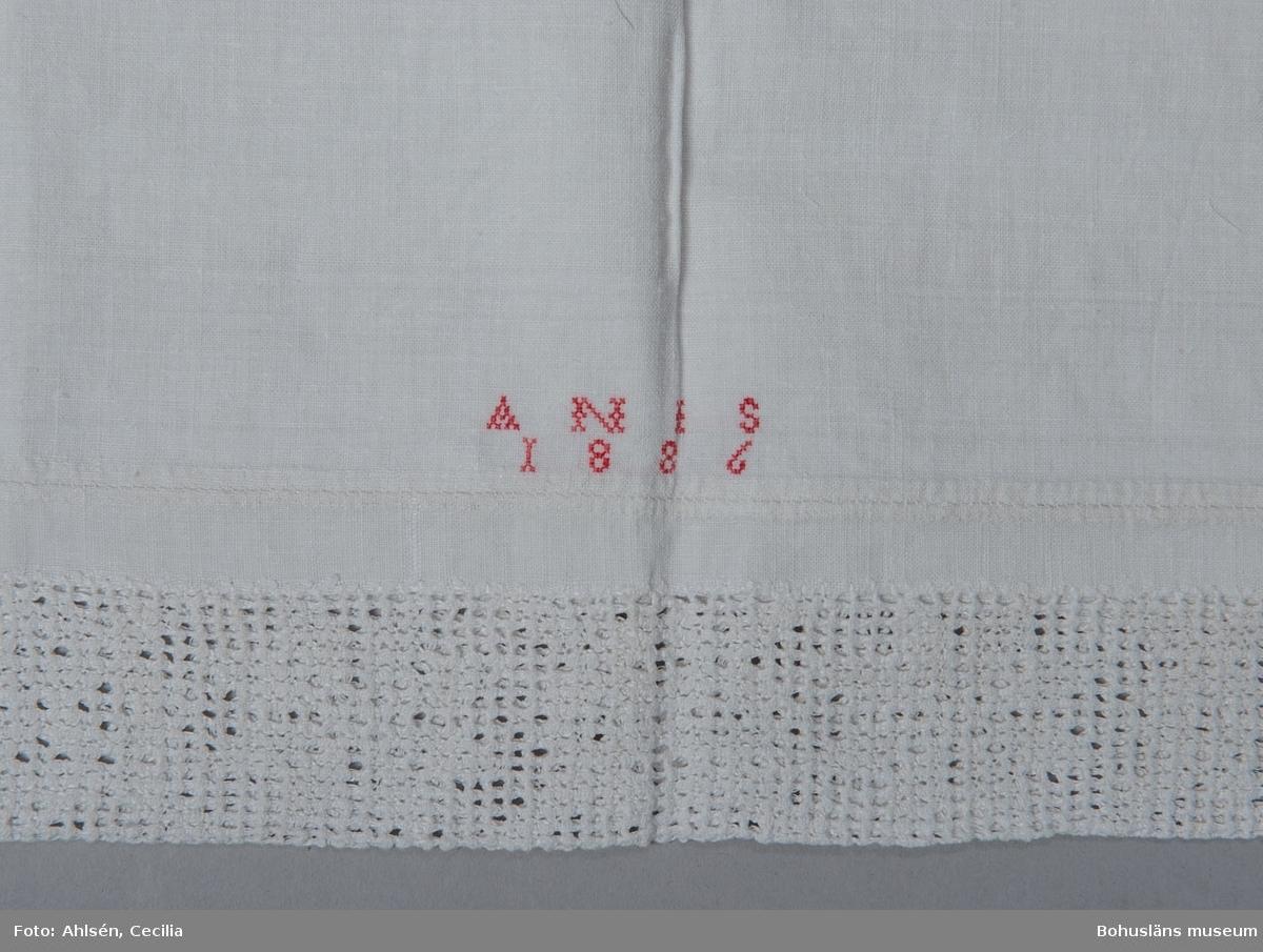 Långörngott av vit handvävd linnelärft, vådbredd 65,5 cm. Sydd (handsydd) som en avlång påse med öppning i ena kortsidan och en infällt hålsömsbroderi i den andra. Mitt inunder spetsen märkt med A N I S 1889 i korsstygn med rött bomullsgarn. Den 6 cm breda spetsen är sydd i vitt lingarn direkt i väven i utskårssöm, en hålsöm med utskurna hål. Mönstret bildar åttuddiga stjärnor. Partiet är sedan dubbelvikt och fastsydd vid örngottets stadkant med kastsöm.