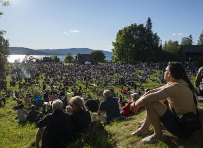 Sola skinner over ei fullsatt gresslette med folk, noen sitter i skråningen ned mot sletta og nyter sola.