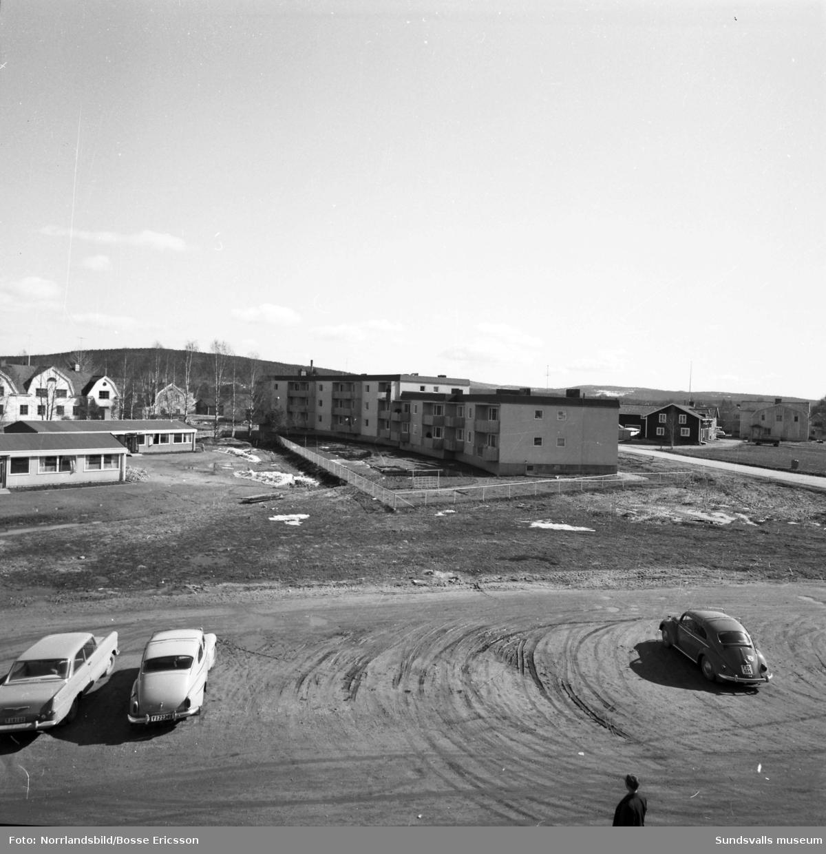 Flerfamiljslänga vid Centrumgatan 22-30. första bilden syns delar av Matfors skola till vänster och bakom björkarna byggnaden där Norrlands Bank huserade samt Röhmans affär, båda rivna. På andra bilden syns gamla bankhuset till höger.