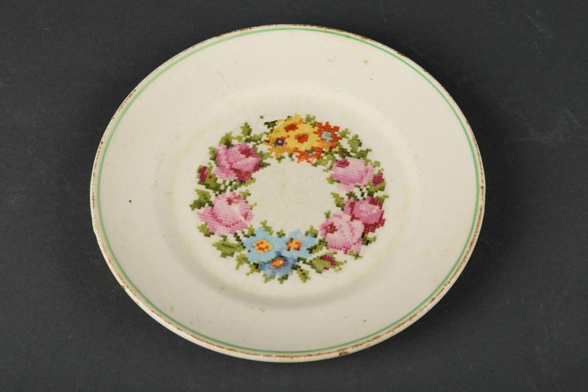 7 Hvite tallerkner med blå håndmalt dekor av bl.a. blomster.