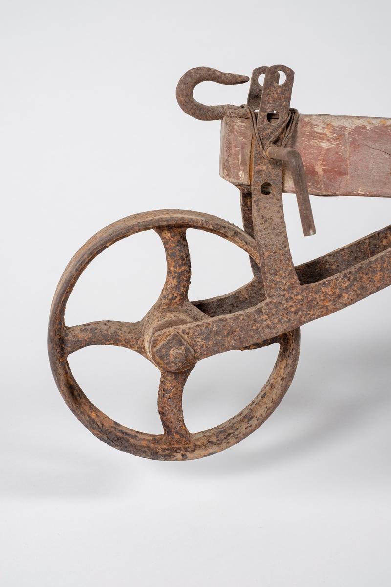 Grubber med ås og styre av tre. I fremkant er det et dybdehjul som kan reguleres i 4 høyder, samt en krok. Rundt låspinnen til hjulet er det fetset ståltråd. Grubberen har et lite skjær midt på ploglegemet, dette kan høydereguleres. I bakkant er det en valse med 26 tinner festet i krans. Mellom styrearmene er det en avstiver av metall. Åsen er satt sammen av tre trestykker. Det er to hull gjennom treverket i de to ytterste trestykkene.
